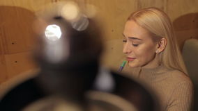 Young beautiful blonde smokes a hookah with a friend in a cafe. stock video footage