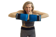 Young beautiful blonde standing in front of a camera screams and holds hands in boxing gloves close-up Royalty Free Stock Images