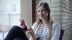 Young beautiful blonde start-upper sits in the modern office, texting on her mobile phone then looks to the camera and stock video