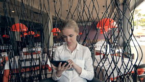 Young beautiful blonde straight hair woman in the city sitting at the restaurant using tablet connected online, looking. Downward and touching the screen stock video footage