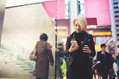 Young beautiful blonde is traveling by work walking on street using 4G internet. Attractive female traveller dressed in stylish casual wear sharing photos from royalty free stock photography