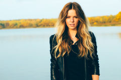 Young beautiful blonde woman in autumn park with lake in dark leather jacket smile perfect teeth during sunset. stock photography