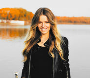 Young beautiful blonde woman in autumn park with lake in dark leather jacket smile perfect teeth during sunset. royalty free stock image