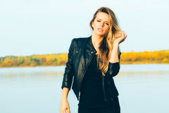 Young beautiful blonde woman in autumn park with lake in dark leather jacket smile perfect teeth during sunset. royalty free stock photo