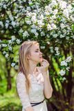 Young beautiful blonde woman in blooming garden. Bride. Closed eyes. Stock Photos