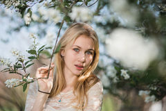 Young beautiful blonde woman in blooming garden. Delicate girl enjoys spring nature Royalty Free Stock Image