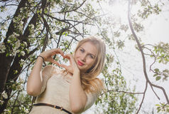 Young beautiful blonde woman in blooming garden. Delicate girl enjoys spring nature Stock Image