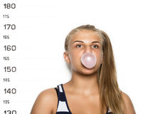 Young beautiful blonde woman chewing gum and blowing bubbles Criminal Mug Shots.  stock image