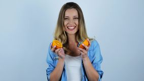 Young beautiful blonde woman dividing cut orange into two parts on isolated white background
