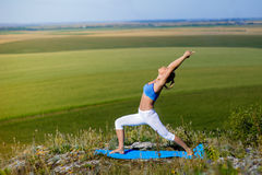 Young beautiful blonde woman doing yoga exercises on a rock. Handstand. Fitness gym and outdoor sports Royalty Free Stock Photo