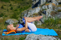 Young beautiful blonde woman doing yoga exercises on a rock. Handstand. Fitness gym and outdoor sports Stock Photos