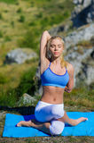Young beautiful blonde woman doing yoga exercises on a rock. Handstand. Fitness gym and outdoor sports Stock Photo