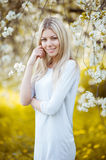 Young beautiful blonde woman in a dress in blooming apple garden Stock Photography