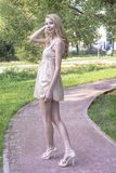 Young beautiful blonde woman in a beautiful dress in a summer park Royalty Free Stock Photo