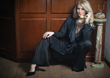 Young beautiful blonde woman in elegant black suit talking by phone sitting relaxed on the floor. Seductive fair hair girl Stock Image