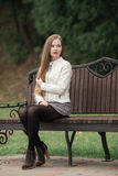Young beautiful blonde woman with extra long straight hair bright red lipstick corrects hairstyle posing on park bench Stock Image