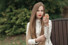 Young beautiful blonde woman with extra long straight hair bright red lipstick holding puff-box looking into camera posing on park Royalty Free Stock Photo