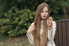 Young beautiful blonde woman with extra long straight hair bright red lipstick holding puff-box looking into mirror and corrects h Stock Photography