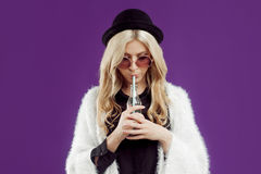 Young beautiful blonde woman in a fashionable hat. Drinking soda from glass bottles. Purple background Stock Photo