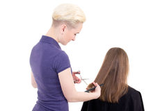 Young beautiful blonde woman hairdresser doing  haircut isolated Stock Photo