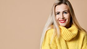 Young beautiful blonde woman happy smiling in big yellow knitted sweater blouse royalty free stock images