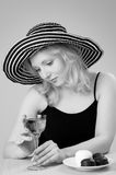 Young beautiful blonde woman in a hat. Young beautiful laughing  blonde woman in a hat  looking and posing with a glass of wine for the camera Stock Photo