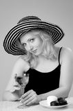 Young beautiful blonde woman in a hat. Young beautiful laughing  blonde woman in a hat  looking and posing with a glass of wine for the camera Stock Photos