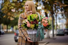 Young and beautiful blonde woman holding a big wicker basket of flowers against the city royalty free stock photos
