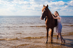 Young beautiful blonde woman and a horse Stock Photos