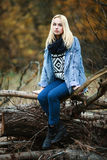 Young beautiful blonde woman in jeans, scarf, and sweater, sitting on logs in autumn forest Stock Image