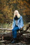Young beautiful blonde woman in jeans, scarf, and sweater, sitting on logs in autumn forest Stock Photo