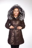Young beautiful blonde woman in a long coat with fur hood. Young beautiful blonde woman in acoat with fur hood Royalty Free Stock Photos