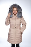 Young beautiful blonde woman in a long coat with fur hood. Young beautiful blonde woman in acoat with fur hood Stock Photo