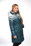 Young beautiful blonde woman in a long coat with fur hood Stock Images