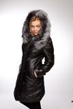 Young beautiful blonde woman in a long coat with fur hood Stock Photos