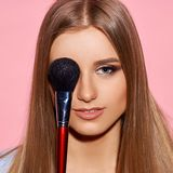 Woman with makeup brush. Young beautiful blonde woman with long hair posing against pink background, holding makeup brush and applying cosmetics Stock Photos