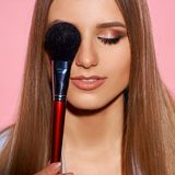 Woman with makeup brush. Young beautiful blonde woman with long hair posing against pink background, holding makeup brush and applying cosmetics Stock Images