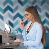Woman applying makeup. Young beautiful blonde woman with long straight hair in blue suit sitting at table in stylish modern interior and applying makeup with Royalty Free Stock Images