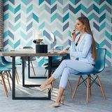 Woman applying makeup. Young beautiful blonde woman with long straight hair in blue suit sitting at table in stylish modern interior and applying makeup with Royalty Free Stock Photo