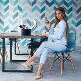 Woman applying makeup. Young beautiful blonde woman with long straight hair in blue suit sitting at table in stylish modern interior and applying makeup with Royalty Free Stock Photography