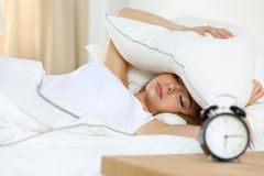 Young beautiful blonde woman lying in bed suffering from alarm c Royalty Free Stock Photos
