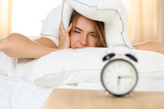 Young beautiful blonde woman lying in bed suffering from alarm c Royalty Free Stock Images