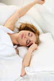 Young beautiful blonde woman lying in bed trying to wake up Stock Photography