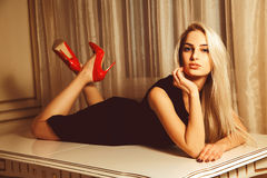 Young beautiful blonde woman lying on table with seduction look Royalty Free Stock Photo
