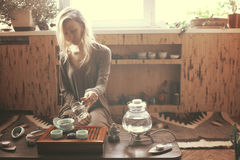 Young beautiful blonde woman. Making tea ceremony royalty free stock photography
