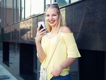 Young beautiful blonde woman with multi colored eyes high bun hairstyle jeans shorts yellow blouse enjoying warm evening posing ag. Ainst city building wall royalty free stock photography