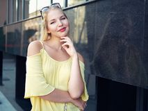 Young beautiful blonde woman with multi colored eyes high bun hairstyle jeans shorts yellow blouse enjoying warm evening posing ag. Ainst city building wall royalty free stock photos