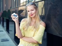 Young beautiful blonde woman with multi colored eyes high bun hairstyle jeans shorts yellow blouse enjoying warm evening posing ag. Ainst city building wall stock photos