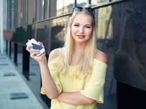 Young beautiful blonde woman with multi colored eyes high bun hairstyle jeans shorts yellow blouse enjoying warm evening posing ag. Ainst city building wall royalty free stock images