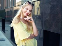 Young beautiful blonde woman with multi colored eyes high bun hairstyle jeans shorts yellow blouse enjoying warm evening posing ag. Ainst city building wall stock photo